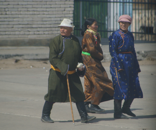 Three Mongols wearing del; train station, April 2005