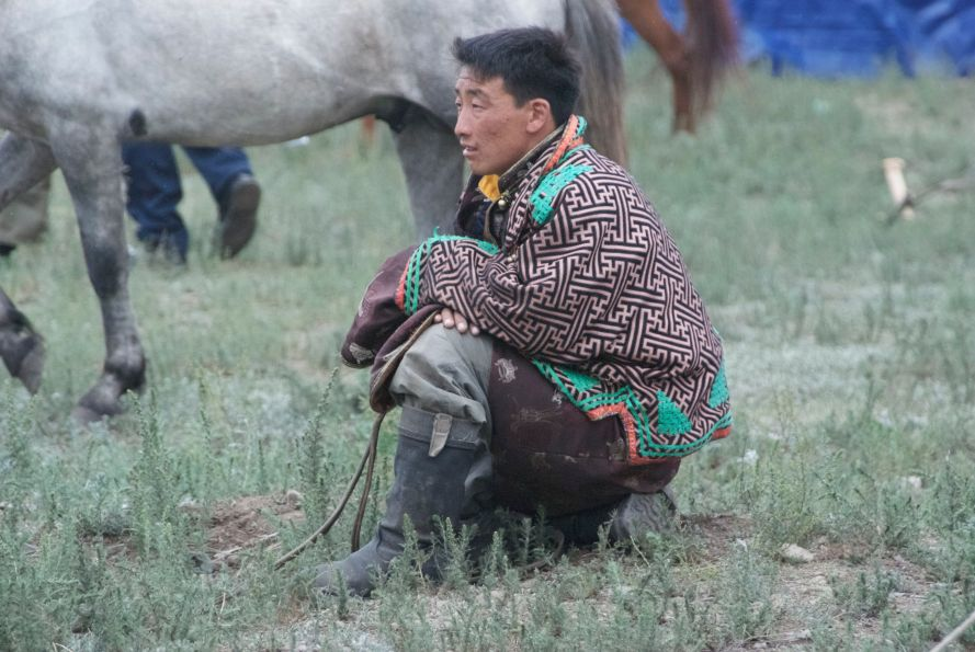 Mongol man kneeling outside of National Stadium