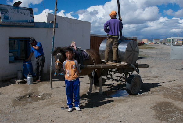 When we arrived at the place to get our water barrel refilled in Bayanhongor, we found that this young boy and his horse-drawn water cart was there ahead of us. A little bribe of candy and he was happy to post for us.