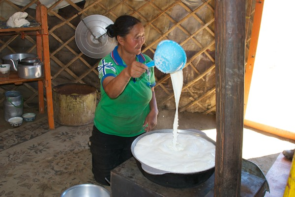 She is heating fresh milk so it will separate the cream.