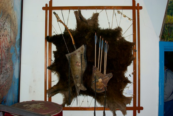 Traditional archery equipment mounted on a bearskin rug.