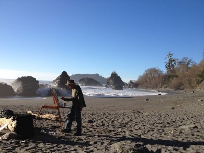 Local artist Steve Porter works on a painting of sunlight coming through the trees on a cliff at one end of the beach.