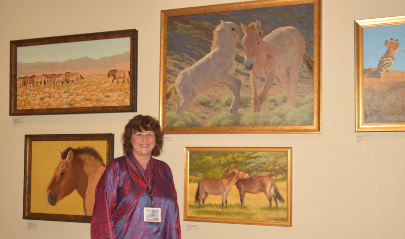 Susan Fox poses with some of her paintings