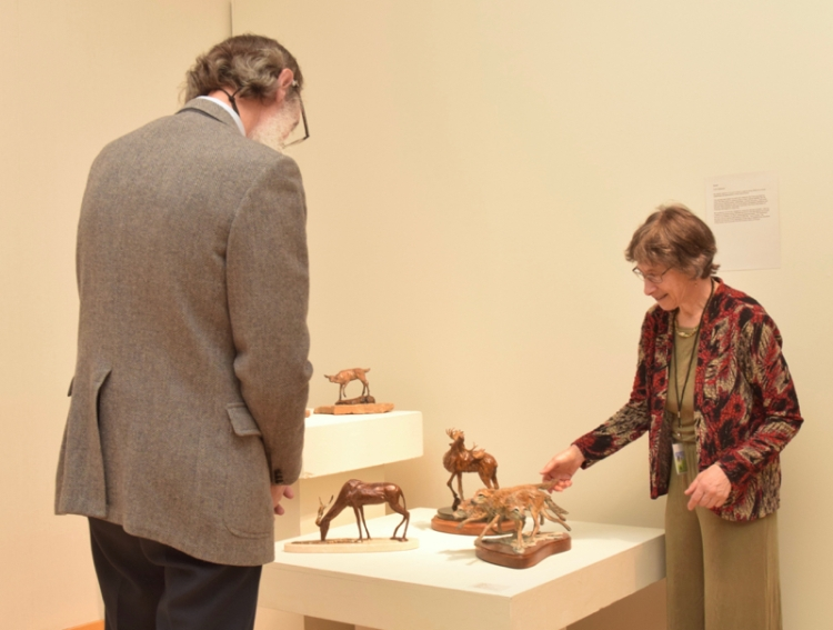 Karryl chats about her sculpture with a guest